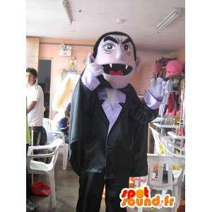 ντυμένη βαμπίρ μασκότ με ένα κοστούμι και μια μαύρη κάπα