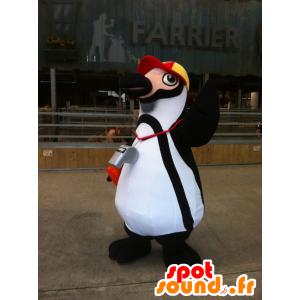 Blanco y negro mascota pingüino con una gorra