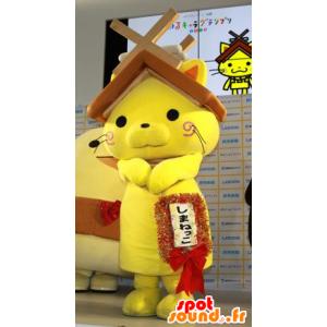 Žlutá kočka maskot s domem střechu nad hlavou