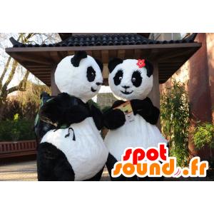 Dois mascotes panda, preto e branco