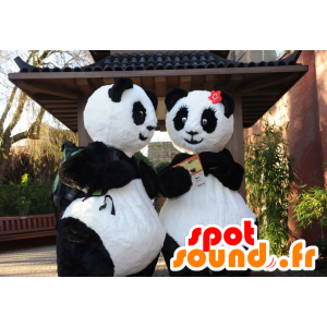Two panda mascots, black and white