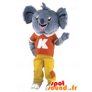 Mascotte de koala gris en tenue rouge et jaune