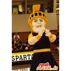 Mascotte de chevalier en tenue noire avec un casque jaune