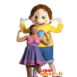 Maskotka chłopiec, ubrany w niebieski i żółty uśmiechnięty uczeń