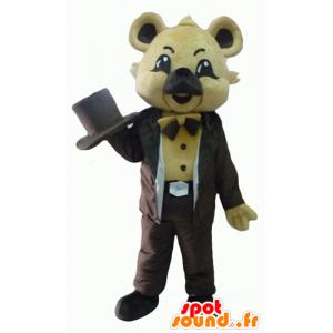 Mascotte de koala beige, en costume marron, avec un chapeau