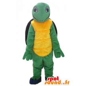 Maskotti keltainen vihreä ja musta kilpikonna, ystävällinen ja hymyilevä