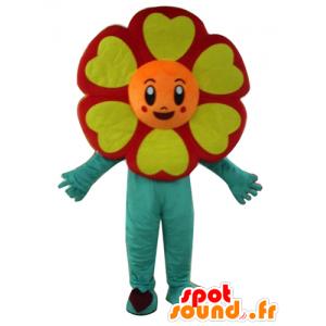 Mascotte de fleur rouge, orange, jaune et verte, très souriante