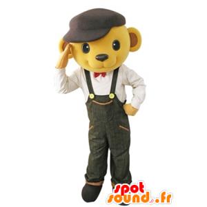Gul bjørnemaskot klædt i overall med en baret - Spotsound