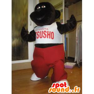 Oscuro mascota del gorila marrón con un traje rojo y blanco