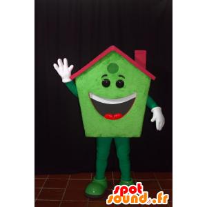 Maskot zelený domov, usměvavý, s červenou střechou