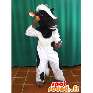 Mascotte de vache noire et blanche avec un casque audio