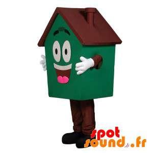 Mascotte de maison géante, verte et marron, très souriante