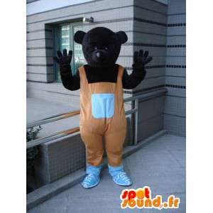 Alle zwarte beer mascotte met oranje overalls en schoenen